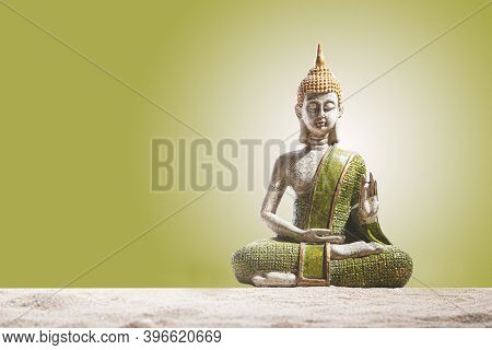 Green And Golden Buddha Statue, On Sand In Green Background.  Meditation, Spirituality And Zen Conce