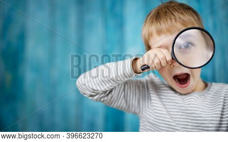 Little Boy Shocked Looking Through A Magnifying Glass