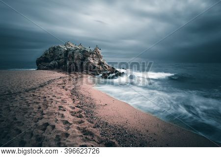 Dramatic Sky With Lonely Rock On The Beach Of Sant Pol De Mar, Catalunya, Spain