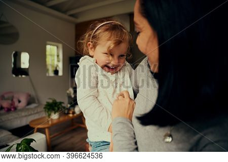 Playful Mother And Daughter Tickling Each Other While Relaxing At Home