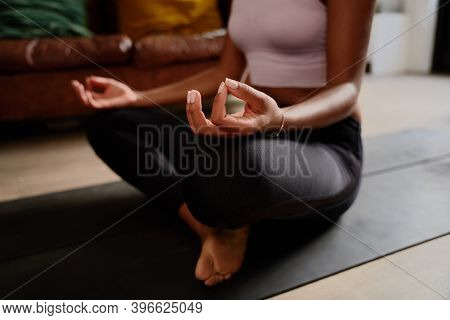 Closeup Of Hands Of Young Woman Sitting In Lotus Position Meditating In The Lotus Pose At Home