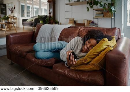 African Woman Lying On Couch Using Smartphone While In Texting Message
