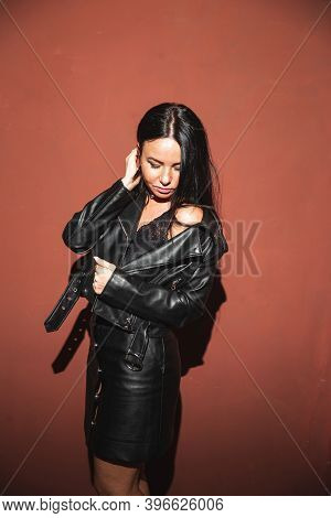 Sexy Brunette Woman In Leather Jacket Leather Skirt And Lace Bralette Posing Red Wall Background Har