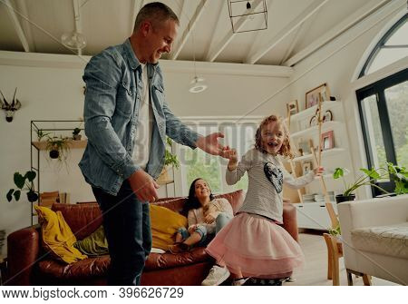 Handsome Young Father Dancing With Daughter At Home While Mother And Sister Sitting On Couch Watchin