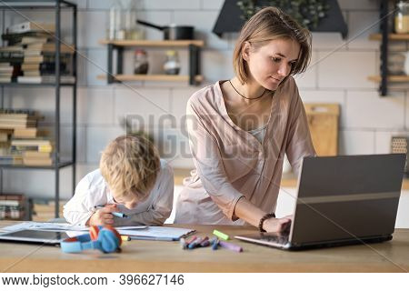 Young Mother With Toddler Child Working On The Computer From Home. Multi Tasking, Freelance And Moth