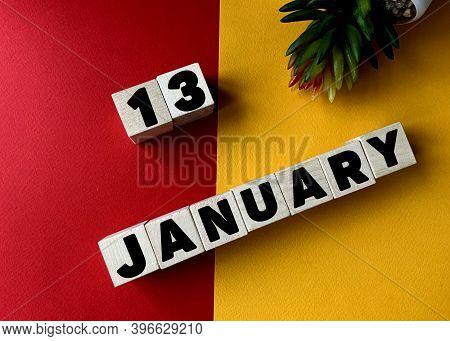 January 13 In Black Letters On Wooden Blocks On A Divided Yellow-red Background .next To A Flower .c