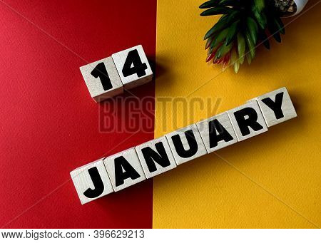 January 14 In Black Letters On Wooden Blocks On A Divided Yellow-red Background .next To A Flower .c