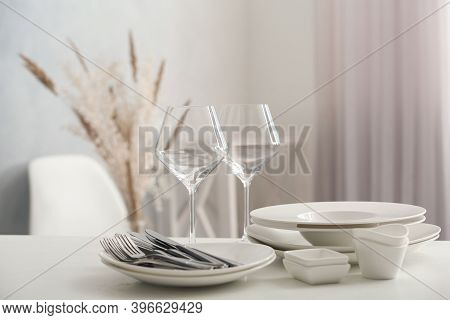 Set Of Clean Dishware, Wineglasses And Cutlery On White Table Indoors