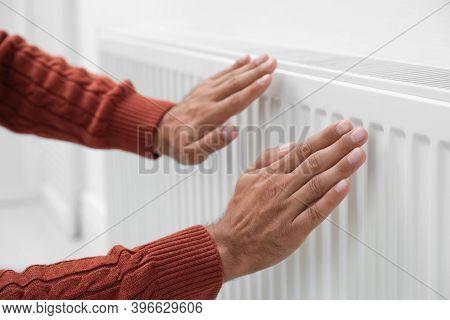 Man Warming Hands On Heating Radiator Near White Wall, Closeup