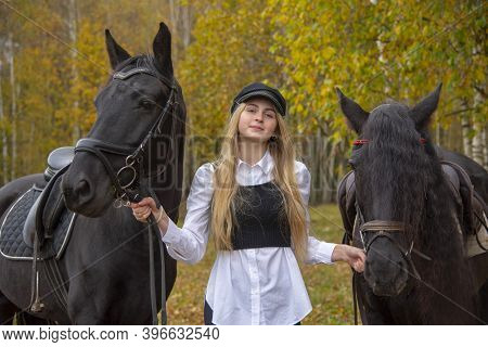 A Young Slender Girl With Blonde Hair Leads Two Horses .