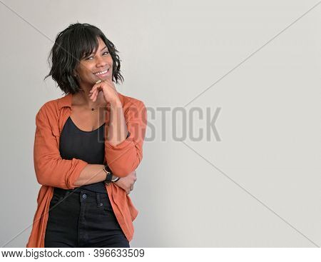 African american woman with red shirt standing on grey background, isolated
