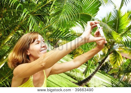 Woman with a smartphone in tropical garden. Vacation.