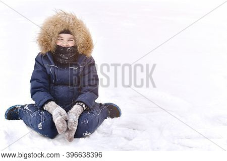 A Child In A Downy Overalls, In Mittens And A Balaclava Gaiter Instead And Smiling Eyes. Sits On Sno