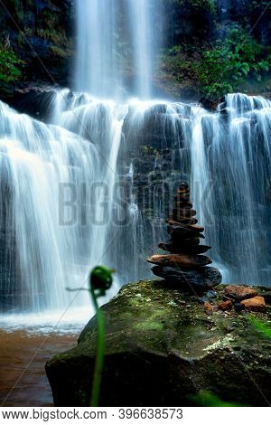 Zen Waterfall With Lush Foliage And Balancing Stones On A Mossy Green Rock In Foreground