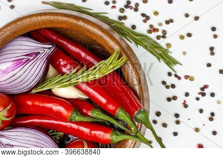 Top View Of Summer Vegetables: Onion, Garlic, Tomato, Red Chili Pepper, Rosemary In Brown Wooden Bow