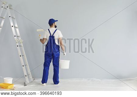 Bearded Painter Contractor Preparing To Paint Wall