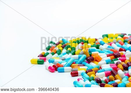 Heap Of Multi-colored Antibiotic Capsule Pills On White Background. Antibiotic Drug Resistance. Anti