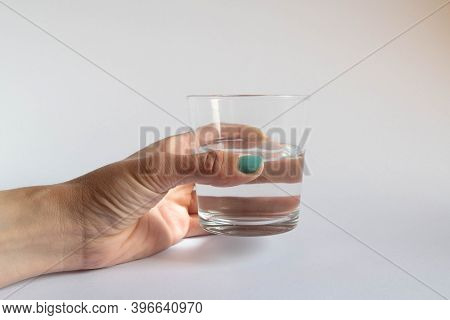 Hand Holding A Glass Half Empty Or Half Full On White Background