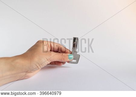 Hand Holding A Key Shaped Pencil Sharpener On White Background