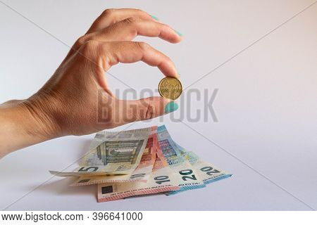 Hand Holding A 20 Cent Coin Over Some Euro Bills On White Background