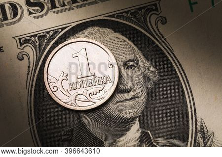 One Russian Kopeck Against The Background Of A Dollar Banknote, Close-up