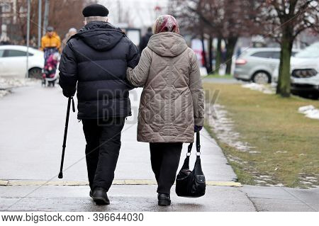 Elderly Woman And Man With Cane Walking Down The Street, Rear View. Old Couple In Warm Clothes In Wi