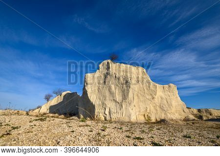 Limestone rock with tree on the top against the blue sky at limestone quarry