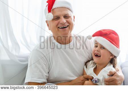 Close-up Portrait Of Joyful Girl Hugging Grandpa In Headwear. Grandfather And Granddaughter In Santa