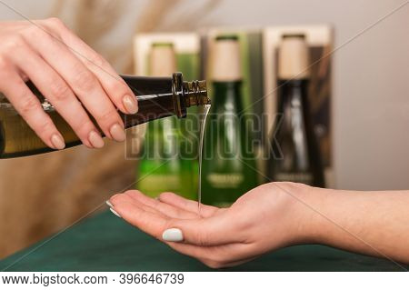 Closeup Of Masseur Hands Pouring Aroma Oil On Woman Back. Masseuse Prepare To Do Oriental Spa Proced
