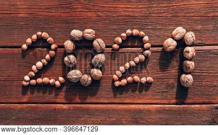 The Inscription 2021 On The Wooden Table Is Made Of Large Walnuts And Hazelnuts. Creative Christmas