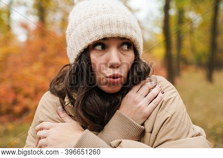 Beautiful unhappy woman in knit hat trembling while strolling in autumn forest