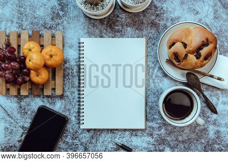 Notebook On The Table, There Is Breakfast Placed On The Side, Top View.