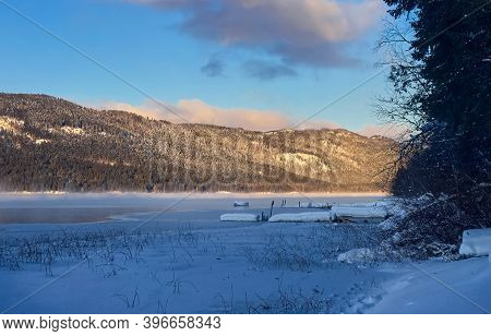 Frozen Mountain White Lake In Winter In The Rays Of Sunset. Snow-covered Wooden Pier. Winter Mountai