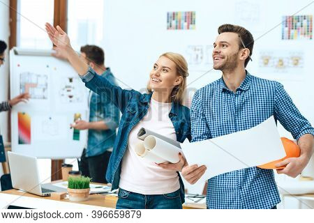 Male Hand Makes A Wooden House In A Bright Office. A Man Made A Wooden House With His Own Hands In T