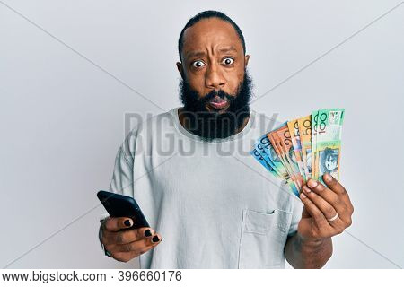 Young african american man using smartphone holding australia dollars banknotes puffing cheeks with funny face. mouth inflated with air, catching air.
