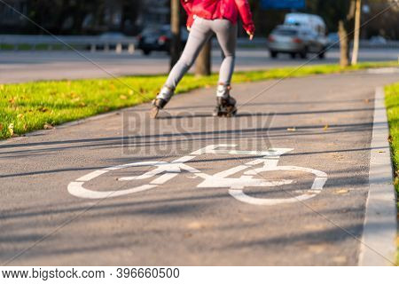 Active Leisure. A Sportive Girl Is Rollerblading In An Autumn Park