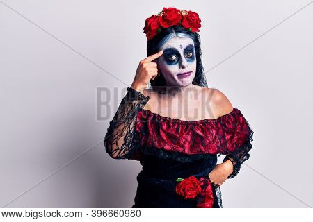 Young woman wearing mexican day of the dead makeup pointing unhappy to pimple on forehead, ugly infection of blackhead. acne and skin problem
