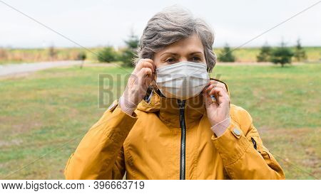 Portrait Elderly Woman Taking Off Her Medical Face Mask. Senior Woman Wearing A Protective Mask Outs