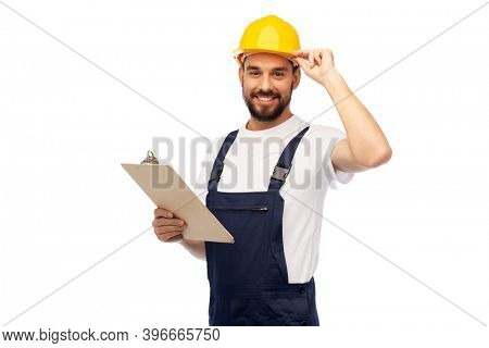 profession, construction and building - happy smiling male worker or builder in helmet with clipboard over white background