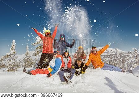 Group Of Young Friends In Colorful Clothes Are Having Fun And Posing At The Top Of Mountain. Winter