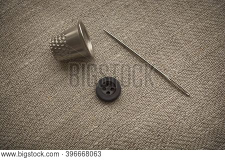 Needle And Button Close-up. Sewing Accessories Lie On The Fabric In Natural Warm Colors.