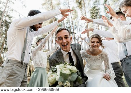 Bride And Groom Run Among The Company Of Friends, Wedding Day Of A Beautiful Couple, Holiday Of Fami