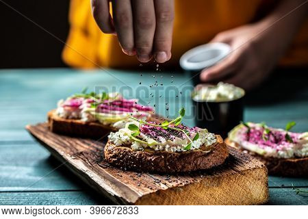 Hand Sprinkling Toast With Chia Seeds With Sliced Watermelon Radish Or Chinese Daikon, Cottage Chees