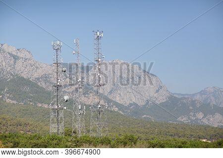 Telecommunication Antenna Tansmitter Tower At Mountains Background.