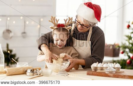 Merry Christmas and Happy Holidays. Family preparation holiday food. Grandma and granddaughter cooking cookies.