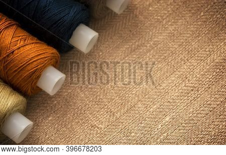 Threads Of Different Colors Lie On The Fabric Of Natural Color. Close Up. The Basis For A Themed Gre