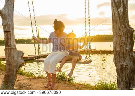 Mother And Child Ride On Wood Swing. Women And Boy Sit On Swing In A Summer At Sunset Time.