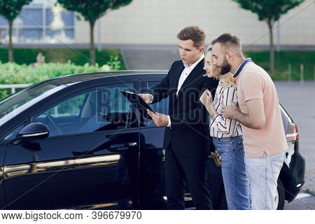 Seller And A Young Couple Outdoors Near A New Car. The Seller Tells The Young Couple About The Car.