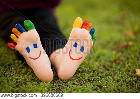 Close Up Of Child Human Pair Of Feet Painted With Smiles Outdoor In Park