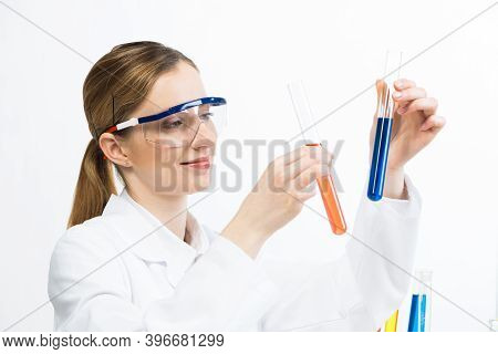 Clinic Laboratory Analysis And Testing. Young Woman In Protective Goggles Holding Test Tube With Col